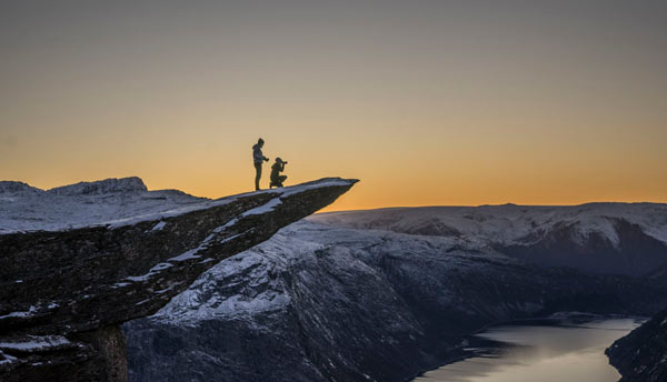 2 people taking photos on tip of trolltunga
