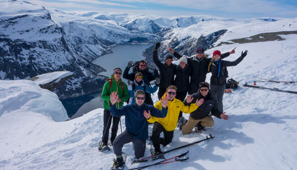 10 people posing in front of Trolltunga with snow